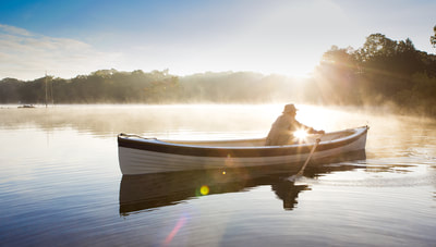 Photo of Man in row boat on foggy lake